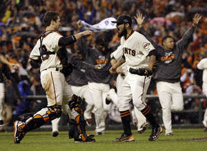 Photo -   San Francisco Giants relief pitcher Sergio Romo and catcher Buster Posey react after the final out in Game 7 of baseball's National League championship series against the St. Louis Cardinals Monday, Oct. 22, 2012, in San Francisco. The Giants won 9-0 to win the series. (AP Photo/David J. Phillip)