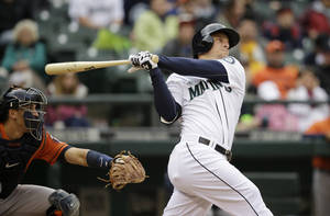 Photo - Seattle Mariners' Kyle Seager, right, hits a three-run walkoff home run as Houston Astros catcher Jason Castro looks on in the ninth inning of a baseball game on Wednesday, April 23, 2014, in Seattle. The Mariners won 5-3. (AP Photo/Elaine Thompson)