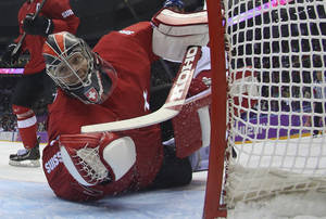 Photo - Switzerland goaltender Jonas Hiller looks for the puck after deflecting a shot by the Czech Republic in the first period of a men's ice hockey game at the 2014 Winter Olympics, Saturday, Feb. 15, 2014, in Sochi, Russia. (AP Photo/Bruce Bennett, Pool)