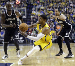 Photo - Indiana Pacers forward Paul George, center, slips as he cuts between Brooklyn Nets forward Kevin Garnett, left, and guard Shaun Livingston in the second half of an NBA basketball game in Indianapolis, Saturday, Feb. 1, 2014. The Pacers defeated the Nets 97-96. (AP Photo/Michael Conroy)