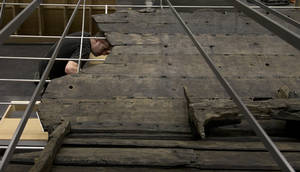 Photo - A conservator helps with the final assembly of The Viking ship known as Roskilde 6, of which about 20 per cent of the timber remains and which is dated to around 1025 AD, at the British Museum in London, Friday, Jan. 17, 2014. The ship was excavated from the banks of Roskilde Fjord, Denmark in 1997. It will be part of a Viking exhibition at the museum that will open to the public on March. 6, 2014. (AP Photo/Alastair Grant)