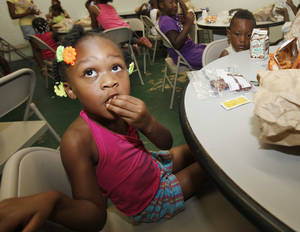 photo - Four year old Serenity Williams eats her lunch during a children's summer camp at the Divine Wisdom Worship Center in Midwest City, OK, Thursday, July 19, 2012,  By Paul Hellstern, The Oklahoman <strong>PAUL HELLSTERN - Oklahoman</strong>