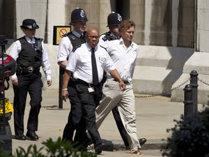 photo -   British police officers escort an man to a waiting police van after he heckled former British Prime Minister Tony Blair poses as he was giving evidence at the Leveson media inquiry at the Royal Courts of Justice in central London, Monday, May 28, 2012. The Leveson inquiry is Britain's media ethics probe that was set up in the wake of the scandal over phone hacking at Rupert Murdoch's News of the World, which was shut in July 2011 after it became clear that the tabloid had systematically broken the law. (AP Photo/Alastair Grant)