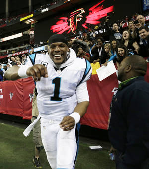 Photo - Carolina Panthers quarterback Cam Newton runs after the second half of an NFL football game against the Atlanta Falcons, Sunday, Dec. 29, 2013, in Atlanta. (AP Photo/Dave Martin)