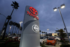 Photo - In this Thursday, Nov. 8, 2012, photo, a Toyota dealership signs glows over a car lot in Tustin Calif. A better economy and extra demand after Superstorm Sandy lifted U.S. auto sales in November. (AP Photo/Chris Carlson)