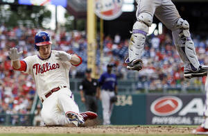 Photo -   Philadelphia Phillies' Chase Utley, left, scores past Colorado Rockies catcher Wilin Rosario on a two-run double by Ryan Howard in the third inning of the first game of a baseball doubleheader, Sunday, Sept. 9, 2012, in Philadelphia. (AP Photo/Matt Slocum)