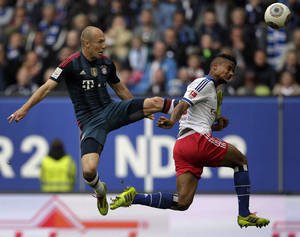 Photo - Hamburg's Michael Mancienne of England, right, and Bayern's Arjen Robben of the Netherlands, left, challenge for the ball during the German Bundesliga soccer match between Hamburger SV and FC Bayern Munich in Hamburg, Germany, Saturday, May 3, 2014. (AP Photo/Michael Sohn)