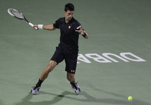Photo - Novak Djokovic of Serbia returns the ball to Spain's Roberto Bautista-Agut during the third day of the Dubai Tennis Championships in Dubai, United Arab Emirates, Wednesday, Feb. 26, 2014. (AP Photo/Kamran Jebreili)