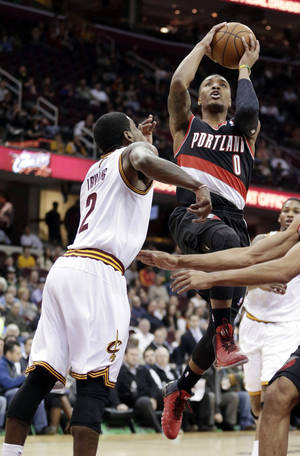 Photo - Portland Trail Blazers' Damian Lillard (0) jumps to the basket against Cleveland Cavaliers' Kyrie Irving (2) during the first quarter of an NBA basketball game Tuesday, Dec. 17, 2013, in Cleveland. (AP Photo/Tony Dejak)