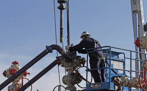 Photo -   Perforating tools, used to create fractures in the rock, are lowered into one of six wells during a hydraulic fracturing operation at an Encana Corp. well pad near Mead, Colo.  AP File Photo  <strong>Brennan Linsley -   </strong>