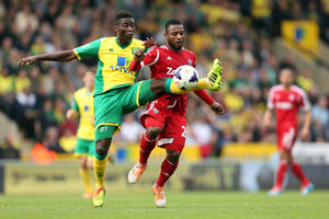 Photo - Norwich City's Alex Tettey, left, is challenged by West Bromwich Albion's Stephane Sessegnon during the English Premier League soccer match at Carrow Road, Norwich, England, Saturday April 5, 2014. (AP Photo/PA, Chris Radburn) UNITED KINGDOM OUT  NO SALES  NO ARCHIVE