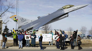 """Photo - FILE - In this March 17, 2014 file photo protesters rally outside the Iowa Air National Guard base, in Des Moines, Iowa. Seven protesters, who were rallying against the use of drones to carry out military strikes, were arrested at the base. Diplomats in Geneva, Switzerland on Tuesday, May 13, 2014 began discussing for the first time at the United Nations whether new international laws are needed to govern the use of """"killer robots"""" _ so-called lethal autonomous weapons systems that could go beyond human-directed drones _ if emerging technologies make their development possible. (AP Photo/Charlie Neibergall, File)"""