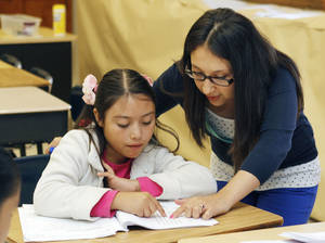 Photo - Instructor Deivi Santizo works with student Yaneli Canedo during a summer reading program at Heronville Elementary School in Oklahoma City, OK, Thursday, June 13, 2013,  Photo by Paul Hellstern, The Oklahoman