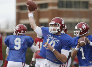 Photo - FILE - In this Tuesday, March 12, 2013, file photo, Oklahoma quarterback Blake Bell (10) throws during a spring NCAA college football practice in Norman, Okla.  The competition to replace starting quarterback Landry Jones will go in front of the public eye for likely the only time when Oklahoma plays its spring game Saturday. Blake Bell, Kendal Thompson and Trevor Knight have been competing for the job during the Sooners' closed practices. (AP Photo/Sue Ogrocki, File) ORG XMIT: OKSO101