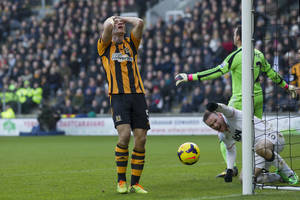 Photo - Hull City's James Chester, left, reacts after scoring an own goal under pressure from Manchester United's Wayne Rooney, bottom right, during their English Premier League soccer match at the KC Stadium, Hull, England, Thursday Dec. 26, 2013. (AP Photo/Jon Super)