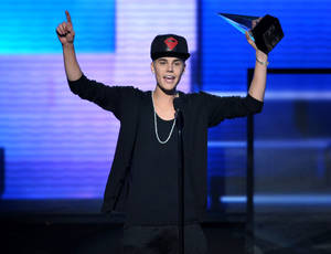 "Photo - FILE - In this Nov. 18, 2012 file photo, Justin Bieber accepts the award for favorite album - pop/rock for ""Believe"" at the 40th Anniversary American Music Awards, in Los Angeles. On Jan. 1, 2013, a paparazzo was struck by a car and killed in Los Angeles while pursuing photos of Bieber's white Ferrari. Bieber was not in the car. (Photo by John Shearer/Invision/AP, File)"