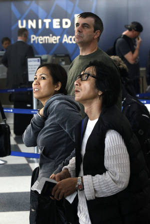 photo -   United Airlines passengers look at the flight schedule displays at Chicago's O'Hare International Airport Thursday, Nov. 15, 2012. Passengers in several cities say a massive computer outage has stranded United passengers at airports across the country, resulting in at least the third major computer outage for the Chicago-based airline since June. (AP Photo/Charles Rex Arbogast)