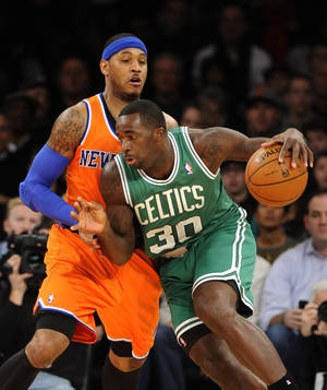 Photo - Boston Celtics power' Brandon Bass (30) drives the ball around New York Knicks Carmelo Anthony (7) in the first half an NBA basketball game on Sunday, Dec. 8, 2013, in New York. (AP Photo/Kathy Kmonicek)