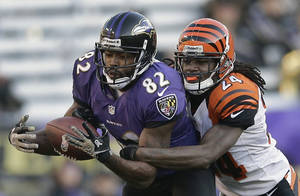 Photo - Cincinnati Bengals cornerback Adam Jones, right, breaks up a pass intended for Baltimore Ravens wide receiver Torrey Smith during the second half of an NFL football game in Baltimore, Sunday, Nov. 10, 2013. (AP Photo/Patrick Semansky)