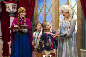 "Photo - This Nov. 15, 2013 photo released by Disney shows unidentified Epcot guests meeting Disney characters Anna, left, and her sister Elsa from the animated film ""Frozen"" at the Norway Pavilion at Walt Disney World Resort in Lake Buena Vista, Fla. The ""Frozen"" sisters are new to the ranks of Disney character greeters, who range from Snow White to Donald Duck. (AP Photo/Disney, Gene Duncan)"