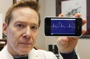 Photo - Dr. David Albert displays his heart monitor device attached to an iPhone at his office in the Research Park in  Oklahoma City. <strong>David McDaniel - The Oklahoman</strong>