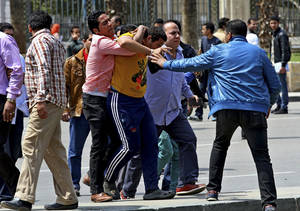 Photo - Plainclothes Egyptian security forces detain people at the scene of deadly explosions that hit the area outside the main campus of Cairo University, in Giza, Egypt, Wednesday, April 2, 2014. Three bombs exploded Wednesday, hitting riot police deployed against near daily protests by Islamist students amid a fierce crackdown by security forces against protesters and supporters of ousted Islamist President Mohammed Morsi. (AP Photo/Hussein Tallal)