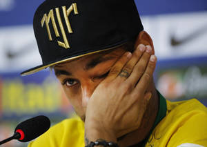 Photo - Brazil's Neymar wipes a tear during a press conference at the Granja Comary training center in Teresopolis, Brazil, Thursday, July 10, 2014. The Brazilian soccer star is back on his feet after suffering a broken vertebrae during a World Cup soccer match against Colombia. Brazil will be disputing a third place finish, without its star on Saturday. (AP Photo/Leo Correa)