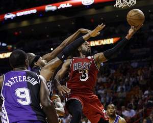 Photo - Sacramento Kings' Patrick Patterson (9) watches as DeMarcus Cousins (15) tries to block Miami Heat's Dwyane Wade (3) during the first half of an NBA basketball game in Miami, Tuesday, Feb. 26, 2013. (AP Photo/J Pat Carter)