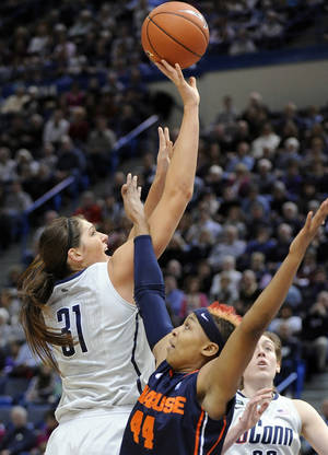 photo - Connecticut's Stephanie Dolson, left, drives past Syracuse's Carmen Tyson-Thomas during the first half of an NCAA college basketball game in Hartford, Conn., Saturday, Jan. 19, 2013. (AP Photo/Fred Beckham)