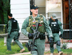 photo - Officers are shown outside a Mustang home Tuesday after making entry at dawn as part of a multiagency drug raid that targeted meth operations throughout the state. Oklahoma Bureau of Narcotics and Dangerous Drug Control officers teamed with U.S. Immigration and Customs Enforcement agents and local law enforcement to execute 13 search warrants and 18 arrest warrants. Photos by Jim Beckel, The Oklahoman