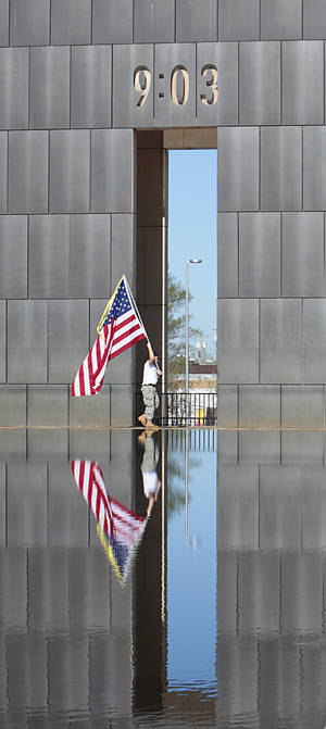 Photo - Retired Staff Sargent Ted Bryan Krey carries a flag by the reflecting pool during the 18th Anniversary Remembrance Ceremony at the Oklahoma City National Memorial and Museum, Friday, April 19, 2013. Photo By David McDaniel/The Oklahoman