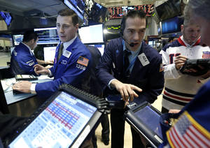 Photo - FILE - In this Friday, Feb. 21, 2014, file photo, trader Gregory Rowe, center, works at the post of specialist Joseph Mastrolia, left, on the floor of the New York Stock Exchange. The mood in financial markets steadied Monday, March 10, 2014, despite earlier big losses in Asia following disappointing Chinese and Japanese economic data. (AP Photo/Richard Drew, File)