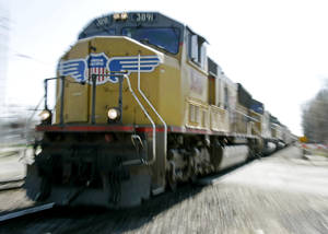 Photo - FILE - In this Tuesday, April 22, 2008, file photo, a Union Pacific train travels through Council Bluffs, Iowa.  Union Pacific's fourth-quarter profit chugged ahead 7 percent in 2012 because the railroad raised shipping rates and collected more fuel surcharges. (AP Photo/Nati Harnik, File)