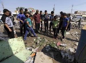 photo -   People gather at the scene of a bomb attack in the neighborhood of Bawiya in eastern Baghdad, Iraq, Saturday, Oct. 27, 2012. A bombing near a playground and other insurgent attacks killed 18 people including several children in Iraq on Saturday, police said. (AP Photo/Khalid Mohammed)