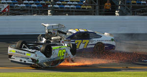 Photo - Parker Kligerman (30) slides on his roof after crashing during practice for Sunday's NASCAR Daytona 500 Sprint Cup Series auto race at Daytona International Speedway, Wednesday, Feb. 19, 2014 ,as Dave Blaney (77) drives past. (AP Photo/News-Journal, Nigel Cook)