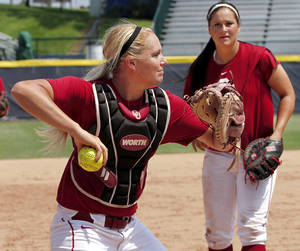photo - COLLEGE SOFTBALL / UNIVERSITY OF OKLAHOMA: OU catcher Jessica Shults  throws to an infielder during practice in preparation for games in the NCAA Women&#039;s College World Series at ASA Hall of Fame Stadium Wednesday, May  30,  2012. In background is Lauren Chamberlain. Photo by Jim Beckel, The Oklahoman