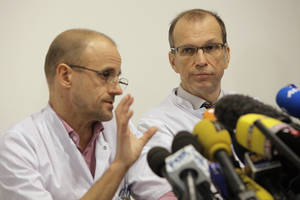 "Photo - Professor Jean-Francois Payen, left, and Emmanuel Gay, right, answer questions from journalists during a press conference at the Grenoble hospital, in the French Alps, where former seven-time Formula One champion Michael Schumacher is being treated after sustaining a head injury during a ski accident in Meribel, France, Tuesday, Dec. 31, 2013. Doctors treating Michael Schumacher refused Monday to predict the outcome for the former Formula One driver, saying they were taking his very critical head injury ""hour by hour"" following his ski accident. Chief anesthesiologist Jean-Francois Payen told reporters that the seven-time champion is still in a medically induced coma. (AP Photo/Laurent Cipriani)"