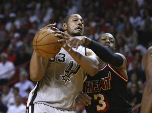 Photo - Miami Heat's Dwyane Wade (3) knocks the ball from San Antonio Spurs' Borks Diaw (33) hands during the first half of a NBA basketball game in Miami, Sunday, Jan. 26, 2014. (AP Photo/J Pat Carter)