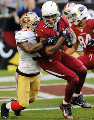 Photo - Arizona Cardinals wide receiver Larry Fitzgerald (11) is stopped short of the goal line by San Francisco 49ers inside linebacker NaVorro Bowman during the first half of an NFL football game, Sunday, Dec. 29, 2013, in Glendale, Ariz. (AP Photo/Matt York)