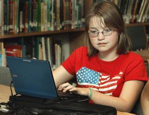 Photo - Lily Schwemley checks out her netbook computer Thursday when Longfellow Middle School students began receiving them at the library. Seventh- and eighth-grade students will have use of their netbooks both on and off campus throughout the school year. PHOTO BY STEVE SISNEY, THE OKLAHOMAN <strong>STEVE SISNEY - STEVE SISNEY</strong>