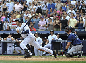 Photo - FILE - In this July 9, 2011 file photo, New York Yankees' Derek Jeter hits a solo home run for his 3,000th career hit off of Tampa Bay Rays starting pitcher David Price in the third inning of a baseball game at Yankee Stadium in New York. Jeter says he will retire after this season. Jeter posted a long letter on his Facebook account Wednesday, Feb. 12, 2014,  saying the 2014 will be his last year playing professional baseball. (AP Photo/Kathy Kmonicek, File)