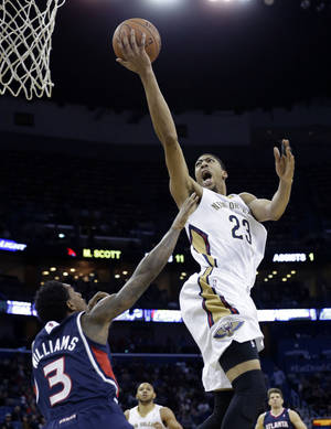 Photo - New Orleans Pelicans power forward Anthony Davis (23) goes to the basket over Atlanta Hawks shooting guard Louis Williams (3) in the second half of an NBA basketball game in New Orleans, Wednesday, Feb. 5, 2014. The Pelicans won 105-100. (AP Photo/Gerald Herbert)