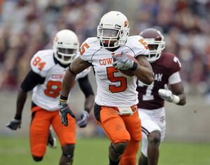 Photo - Oklahoma State running back Keith Toston (5) rushes for a first down as Texas A&M cornerback Terrence Frederick (7) chases him during the first quarter of a NCAA football game Saturday, Oct. 10, 2009 in College Station, Texas.  (AP Photo/David J. Phillip)