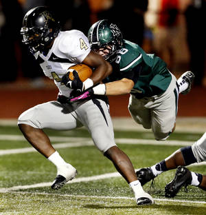 photo - HIGH SCHOOL FOOTBALL PLAYOFFS: Norman North Timberwolf Evan Coles tackles Broken Arrow running back Devon Thomas as the Tigers  play Norman North in Class 6A football on Friday, Nov. 16, 2012 in Norman, Okla.  Photo by Steve Sisney, The Oklahoman