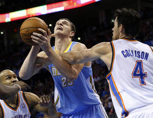 Photo - Denver Nuggets center Timofey Mozqov (25) is fouled by Oklahoma City Thunder power forward Nick Collison (4) in the second quarter of an NBA basketball game in Oklahoma City, Monday, Nov. 18, 2013. (AP Photo/Sue Ogrocki)