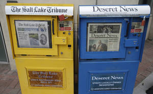 Photo - The Salt Lake Tribune and Deseret News,  newspaper boxes are shown next to each other  Monday, June 16, 2014, in Salt Lake City. A group of former employees of The Salt Lake Tribune have filed a lawsuit to suspend the newspaper's joint operating agreement with the Deseret News, arguing that the terms violate federal antitrust laws and undermine the Tribune's independent voice.   (AP Photo/Rick Bowmer)