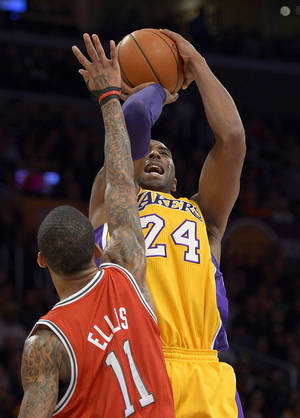Photo - Los Angeles Lakers guard Kobe Bryant, right, puts up a shot as Milwaukee Bucks guard Monta Ellis defends during the first half of their NBA basketball game, Tuesday, Jan. 15, 2013, in Los Angeles. (AP Photo/Mark J. Terrill)
