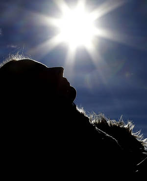 Photo - A woman lays in the sun outside the Swiss House at the 2014 Winter Olympics, Wednesday, Feb. 12, 2014, in Sochi, Russia. Temperatures are predicted near 60 degrees Fahrenheit in Sochi on Wednesday. (AP Photo/Morry Gash)