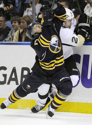 Photo - Buffalo Sabres' Linus Omark (17), of Sweden, grimaces after a check on Pittsburgh Penguins' Matt Niskanen (2) during the first period of an NHL hockey game in Buffalo, N.Y., Wednesday, Feb. 5,  2014. Pittsburg won 5-1.  (AP Photo/Gary Wiepert)