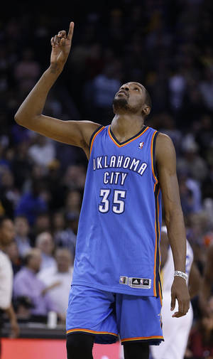 Photo - Oklahoma City Thunder's Kevin Durant points skyward at the end of the NBA basketball game against the Golden State Warriors  Wednesday, Jan. 23, 2013, in Oakland, Calif. (AP Photo/Ben Margot) ORG XMIT: OAS112